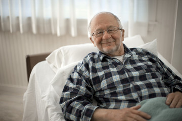 Portrait of a cheerful senior man lying in bed.