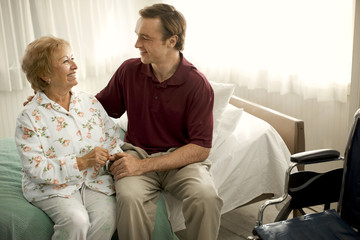 Smiling senior woman speaking with a male nurse on the edge of a bed while holding his hand.