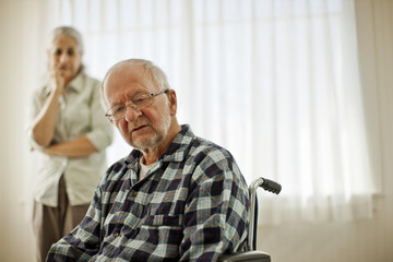 Unhappy senior man sitting in a wheelchair.
