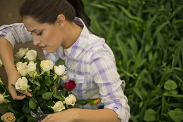Teenage girl making a bouquet of roses.
