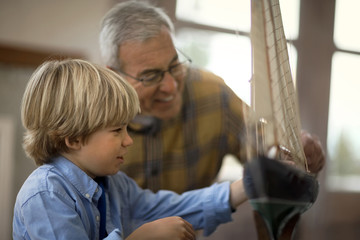 Happy young boy helping his grandfather to build a toy ship in the garage.