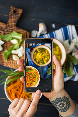 Phone photography of food. Woman hands take photo of lunch with smartphone for social media. Lentil soup with cauliflower. Raw vegan vegetarian healthy dinner