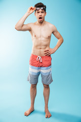 Full length portrait of a shocked young shirtless man