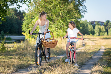 Happy young mother and daughter riding bicycles and looking at each other