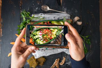 Phone photography of food. Woman hands take photo of lunch with smartphone for social media. Vegetables buddha bowl in avocado bowl. Raw vegan vegetarian healthy dinner