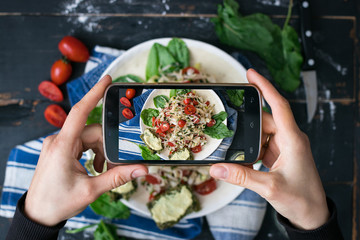 Phone photography of food. Woman hands take photo of lunch with smartphone for social media. Fresh vegetables salad. Cabbage salad with tomatoes. Raw vegan vegetarian healthy dinner