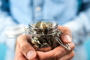 Man holding a coin jar