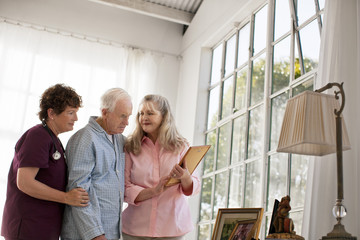 Mature woman and nurse showing old family photographs to a senior man.