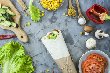 Vegan burrito from vegetables, mushrooms and tortillas. On a gray table among the ingredients. Top view