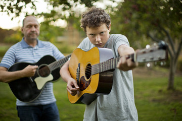Portrait of a father and son practicing playing guitar together.
