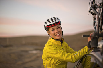 Portrait of a smiling young woman wearing a cycling helmet.