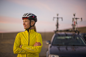 Smiling young woman relaxes in the sunset before she heads home after a day of cycling.