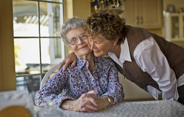 Smiling mature woman greets her cheerful elderly mother as she sits at the kitchen table.