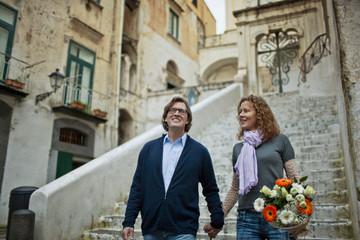 Smiling middle aged couple walking hand in hand down a flight of stone stairs.