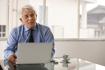 Thoughtful businessman ponders work while sitting in front of a laptop.