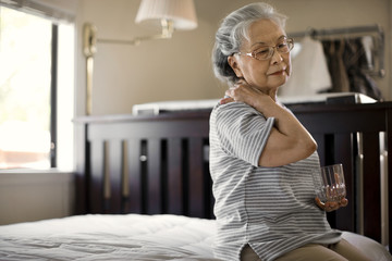 Senior woman sitting on her bed massaging her neck.