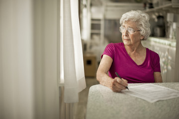 Anxious elderly woman gazes out of the kitchen window as she debates signing some paperwork.