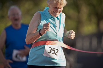 Smiling senior woman crossing the finish line of a running race.