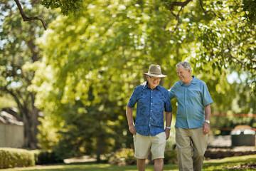 Happy senior men walking through a green leafy park.