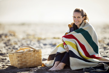 Portrait of a smiling young woman wrapped in a large blanket at the beach.