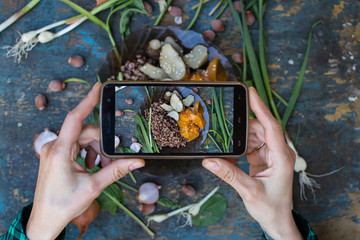 Phone photography of food for social networks.  Smartphone photo of buckwheat porridge with backed pumpkin and Israeli artichoke. Raw vegan vegetarian healthy food
