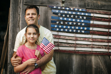 Happy father and daughter standing in front of an American flag.
