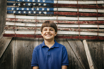 Portrait of a smiling young boy standing in front of an American flag.