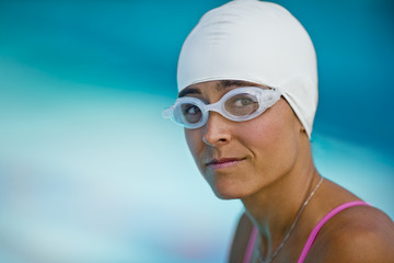 Portrait of a middle aged woman wearing swimming cap and goggles.