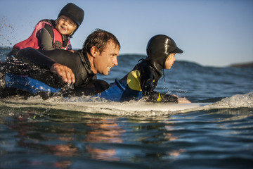 Middle aged man surfing with his two young daughters.