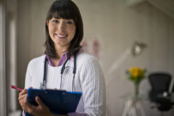 Portrait of a young female doctor holding a clipboard in her office.