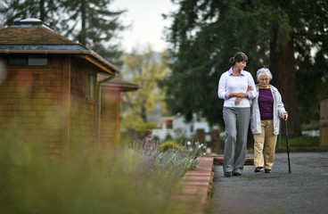 Elderly woman walking arm in arm with her doctor.