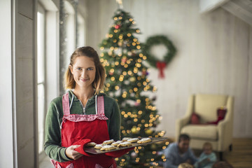 Portrait of a smiling woman holding a tray of freshly baked Christmas cookies.