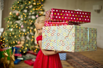 Young girl carrying a stack of Christmas presents.