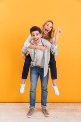 Full length photo of young couple having fun while guy giving piggyback ride to lovely girl showing peace sign, isolated over yellow background