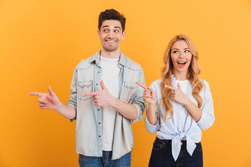 Photo of happy man and woman in basic clothing smiling and pointing finger aside at copyspace, isolated over yellow background