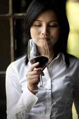 Mid-adult woman holding a glass of red wine.
