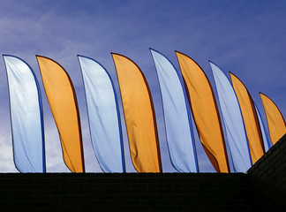 Blue and yellow beach flags against a blue sky