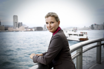 Portrait of a confident mid-adult business woman leaning on a railing at a waterfront next to a harbor.