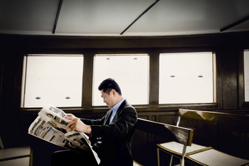 Mid-adult businessman reading a newspaper on a ferry.