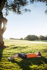 Young boy peacefully lying in a field.