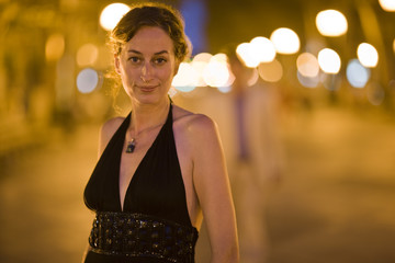 Portrait of a mid-adult woman standing on a lit street in the evening.