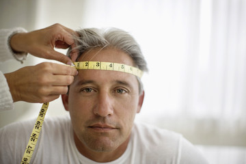 Portrait of a mature man having his head measured with a tape measure.