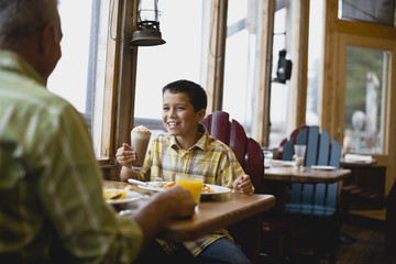 Boy with cream around his face grinning while sitting in a diner with his father.