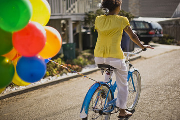 Young woman riding a bicycle with balloons tied to it along a suburban street.