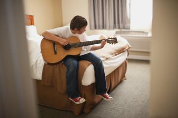 Boy practicing guitar in his bedroom