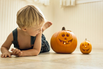 Young boy lies front down on a floor and looks back at a big Jack O'Lantern and a small Jack O'Lantern lit with candles inside next to him as he poses for a portrait.