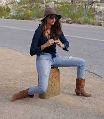 Young woman with hat and sunglasses waiting by the side of the road