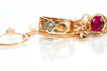 Real gold rings, chains, diamonds and gems on shiny surface, white background.