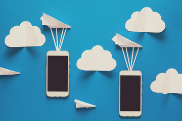Data transfer concept. Message passing. Two mobile smartphones and paper airplanes on blue background. Origami. Paper cut. Toned
