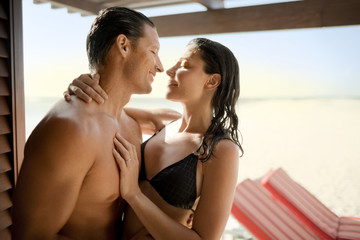 Flirty mid-adult couple leaning in to each other while standing inside a beach resort.